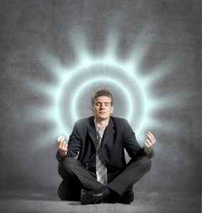 man sitting doing yoga in a suit