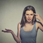 Closeup portrait of angry mad young woman gesturing with her finger against temple asking are you crazy? Isolated on gray wall background. Negative emotions facial expression feeling body language.